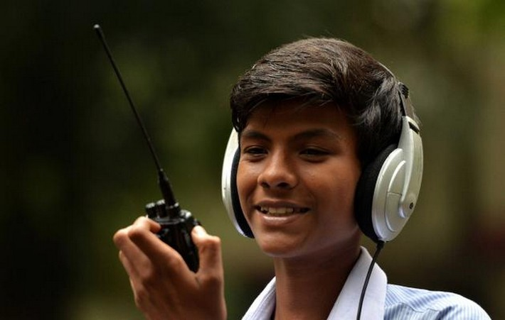 Smiling boy with headset using a hand-held transceiver
